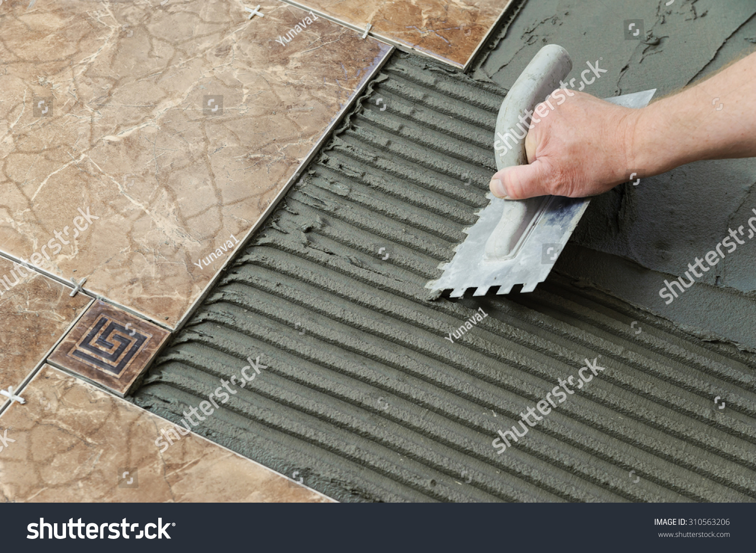 Laying Ceramic Tiles Troweling adhesive onto a concrete floor in preparation for laying white floor tile