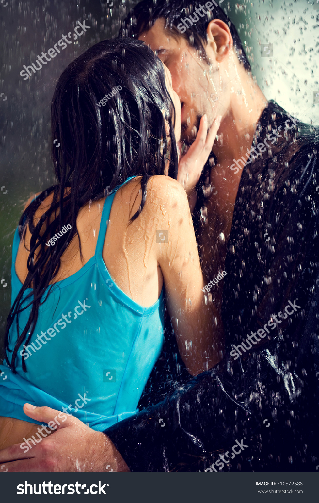 Young hugging couple kissing under a rain in passion