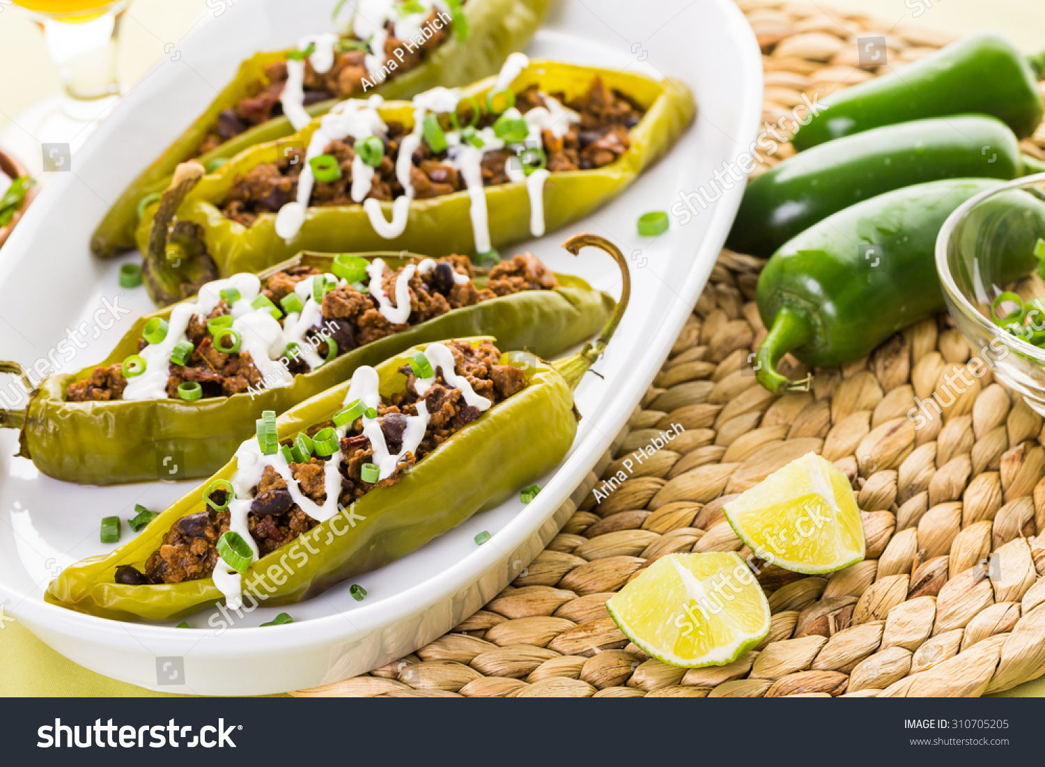 Chipotle beef & bean stuffed chile peppers garnished with sour cream ...