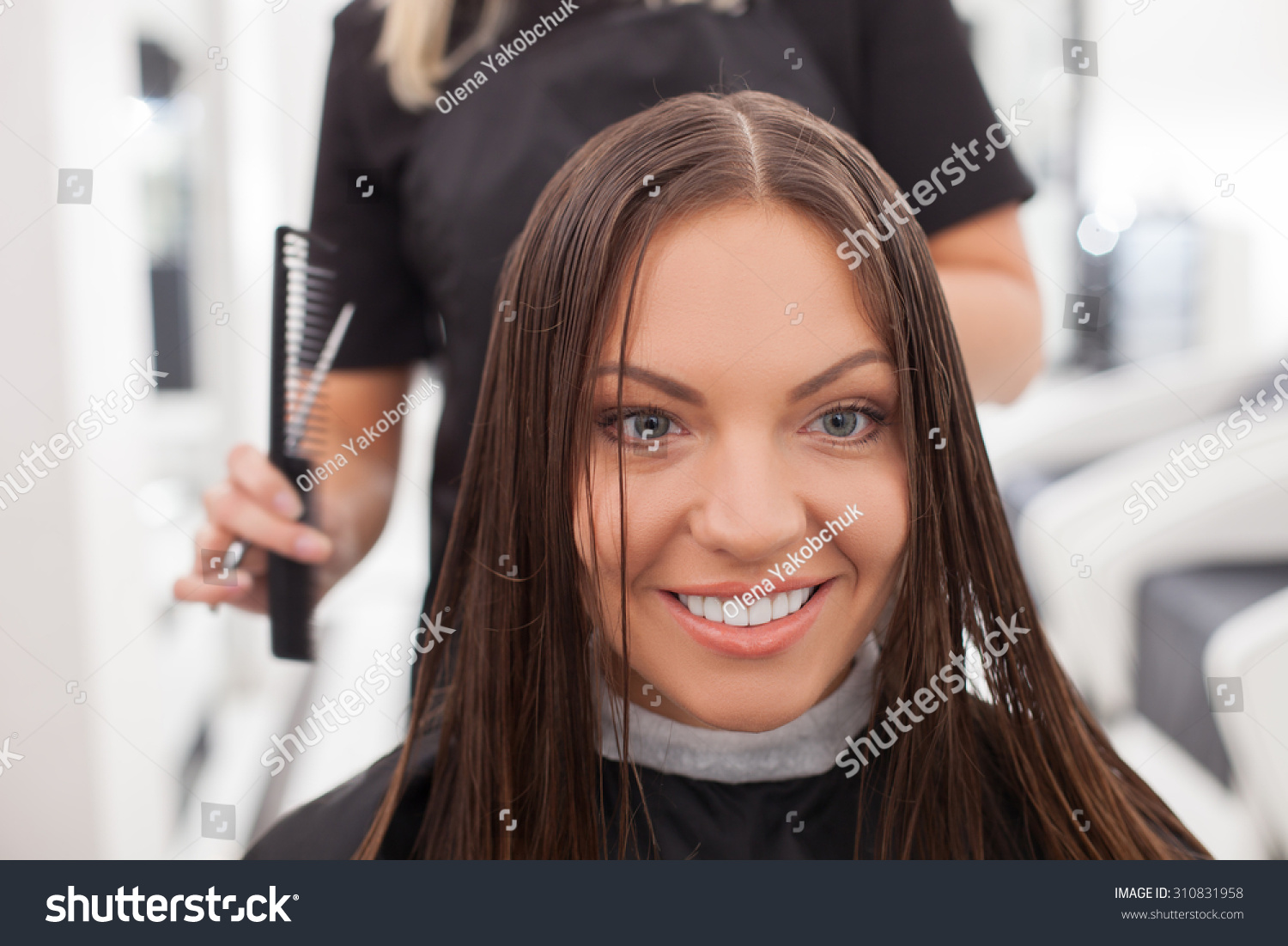 professional hairstylist is making a haircut to her customer she is standing behind the woman - Professional Hairstylist