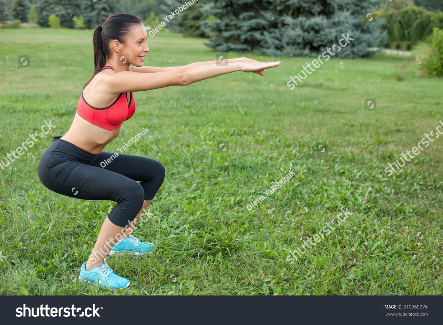 Beautiful woman is doing squats in park She is stretching her arms forward The sportswoman is smiling happily Copy space in right side
