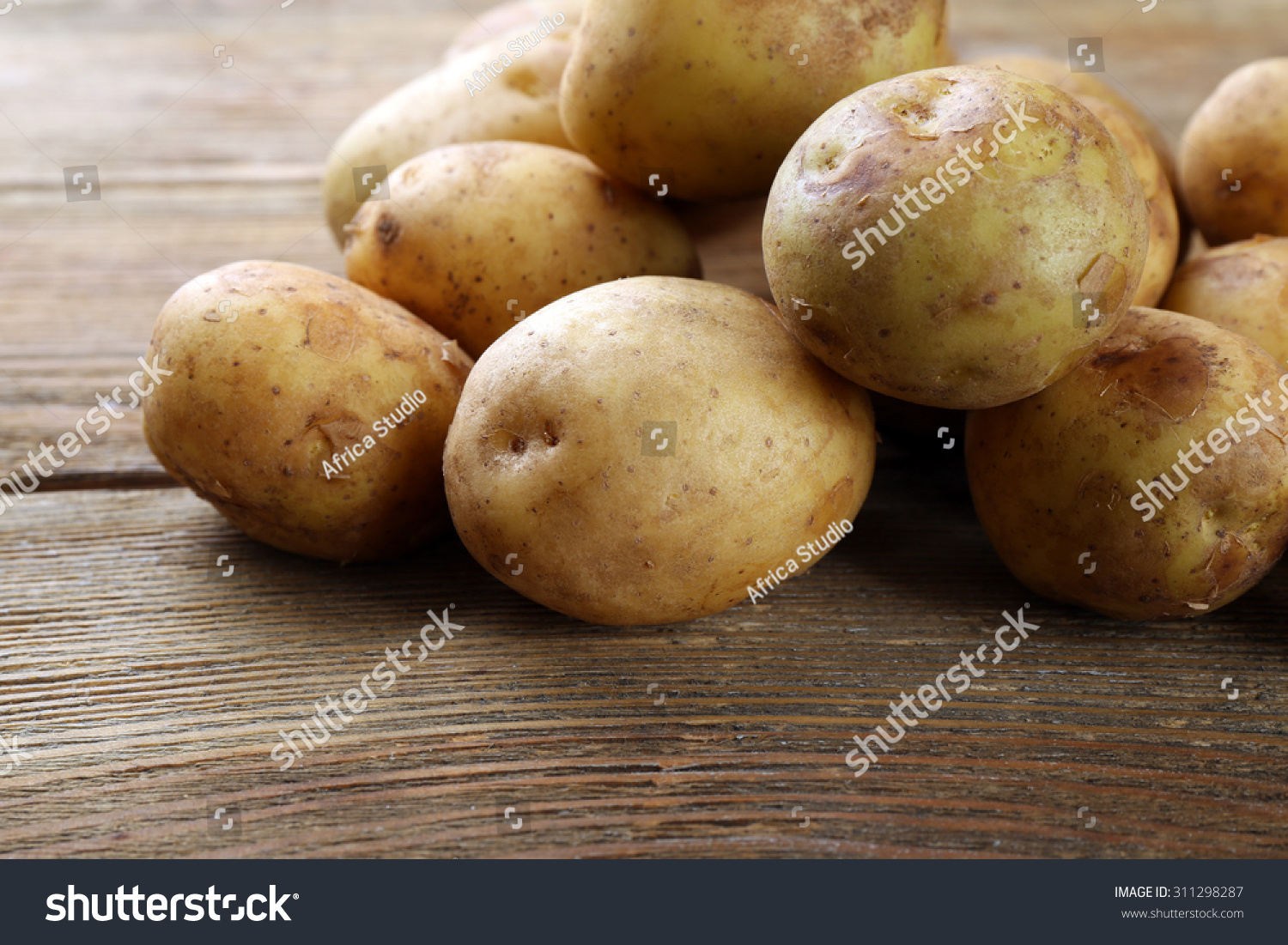 Young potatoes on wooden table close stock photo