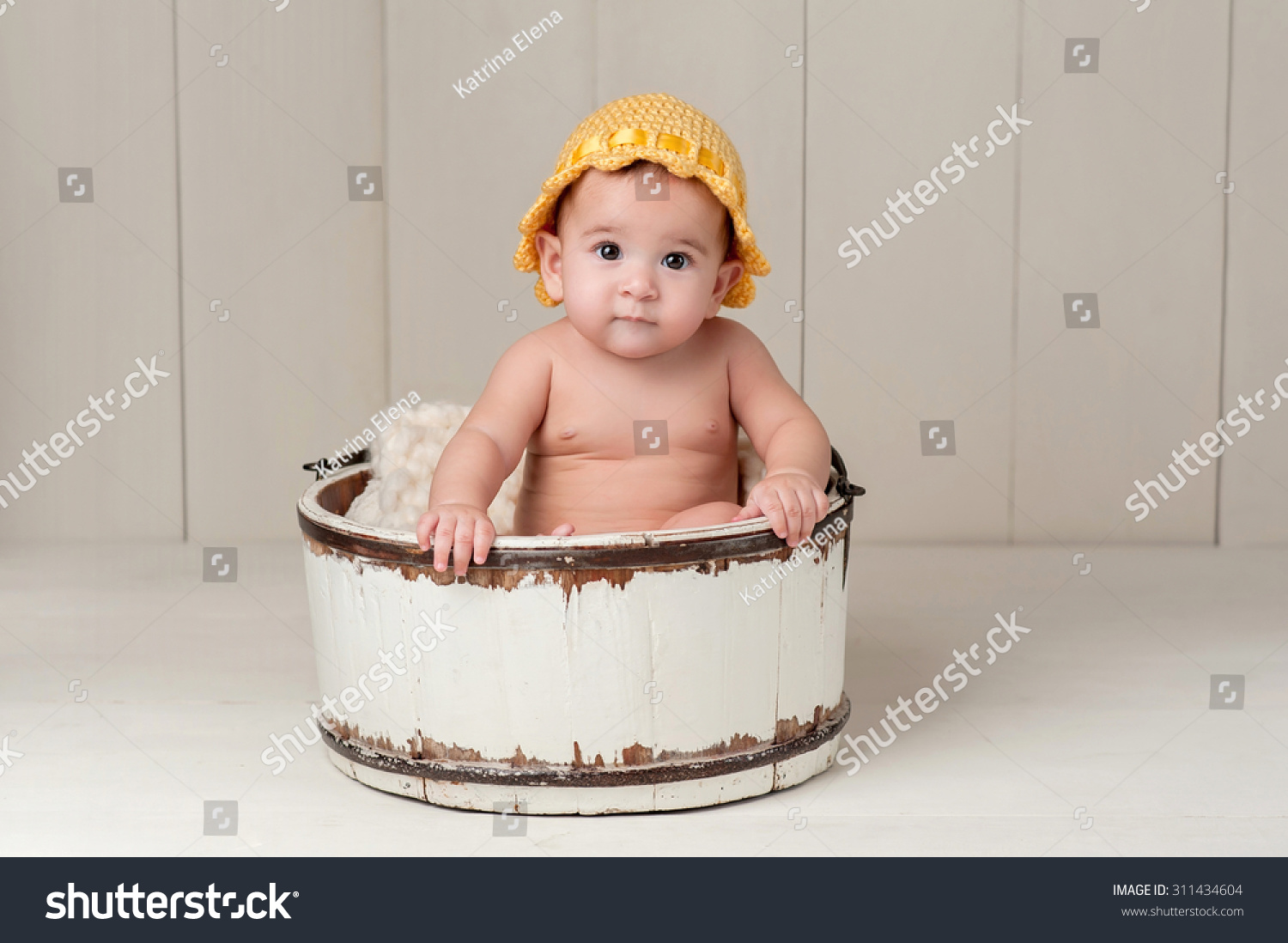 A 6 Month Old Baby Girl Wearing Yellow Knitted Hat And Sitting In Vintage