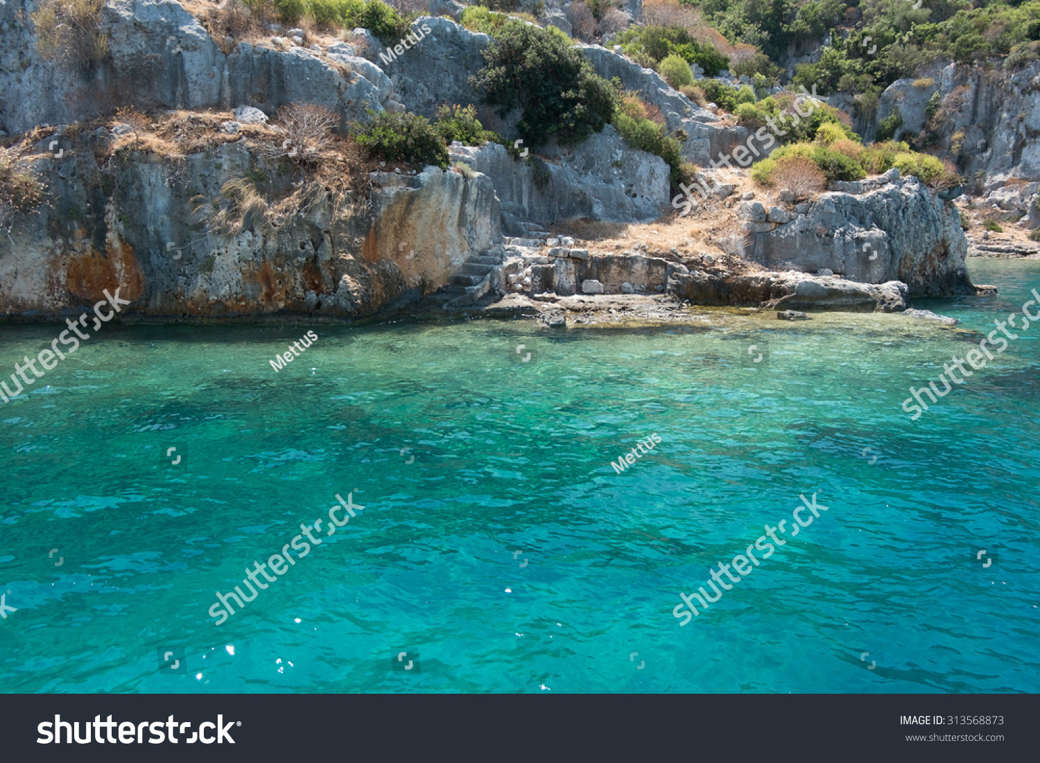 Sea and coast of island. Sea harbor with blue-green water and coast rocks. Beautiful seascape. Composition of nature. A lot of space for text. Tropical island.