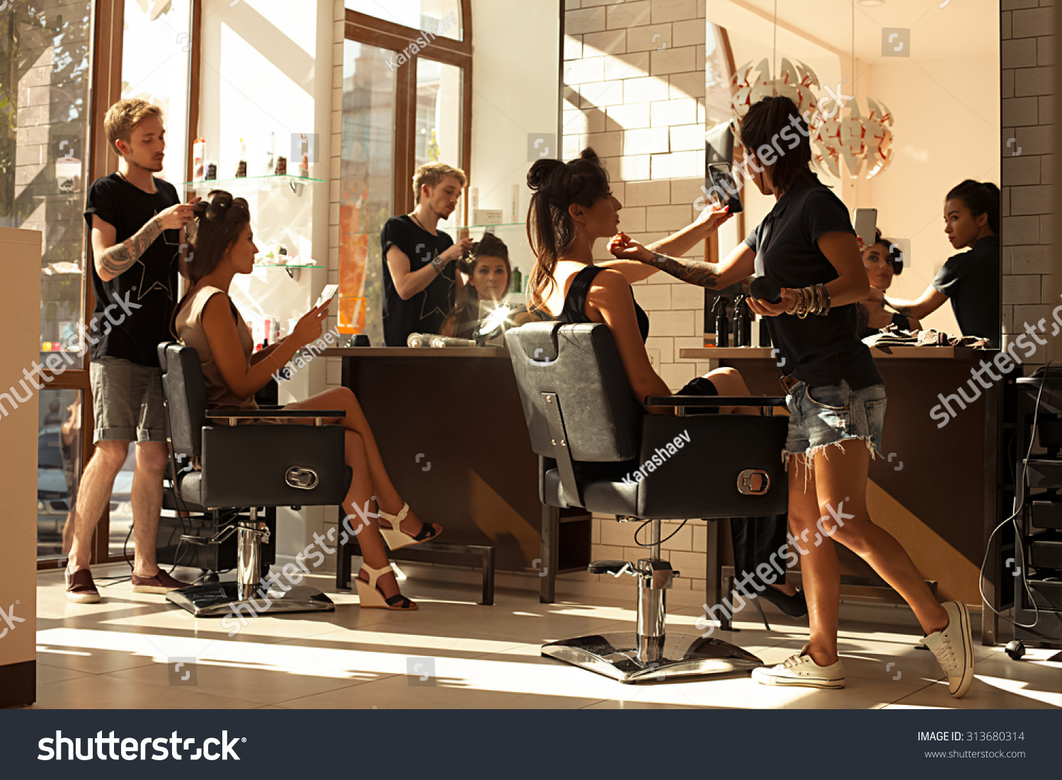 Picture of working day inside the beauty- sit on two chairs clients beautiful young girls. Hairdresser makes hair styling or hair cut, make-up artist doing make-up in a beauty salon- stock photo. #313680314