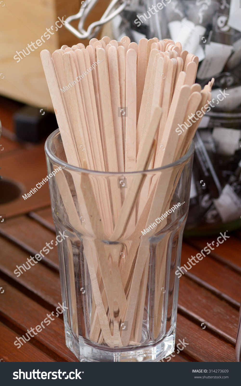 Wooden drink stirrers in glass on table at cafe stock