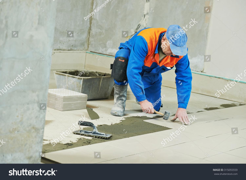 Industrial Tiler Builder Worker Installing Floor Tile At Repair