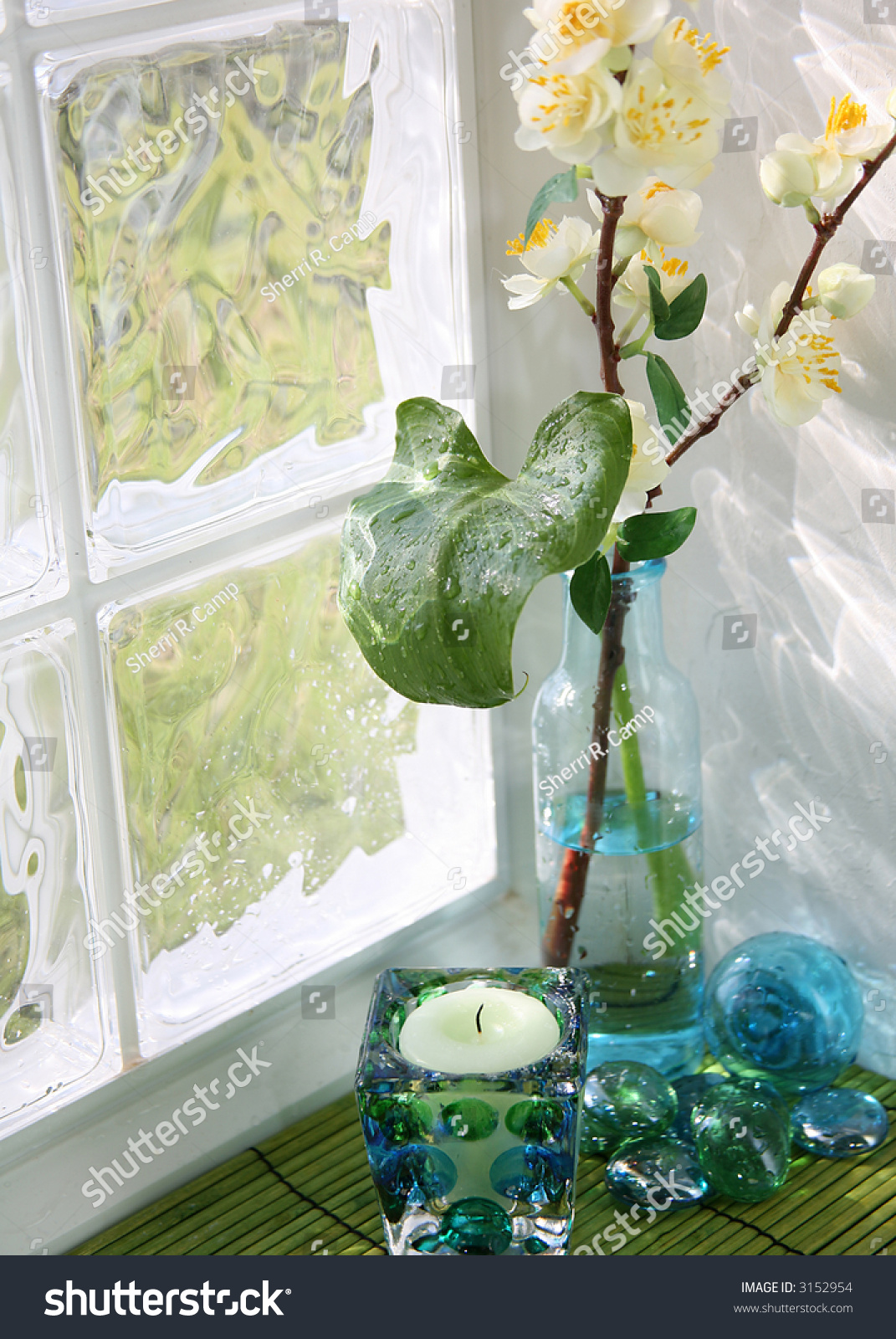 Candle and vase with apple blossoms on glass block window for Glass block r value