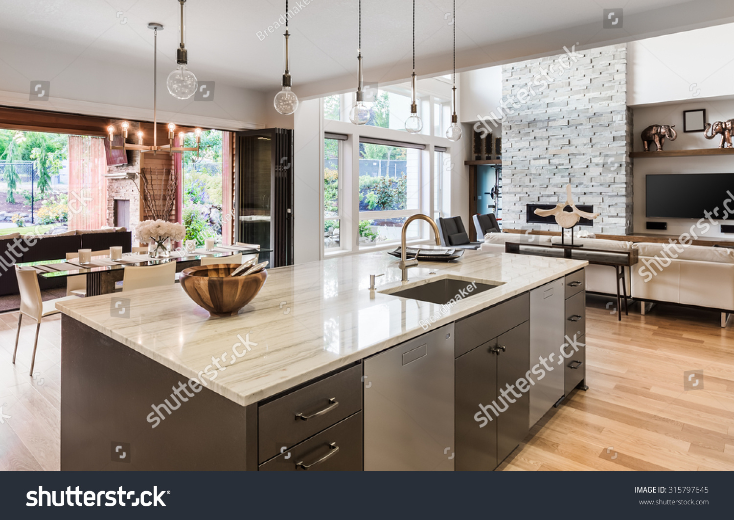 Kitchen With Island, Sink, Cabinets, And Hardwood Floors In New Luxury Home,