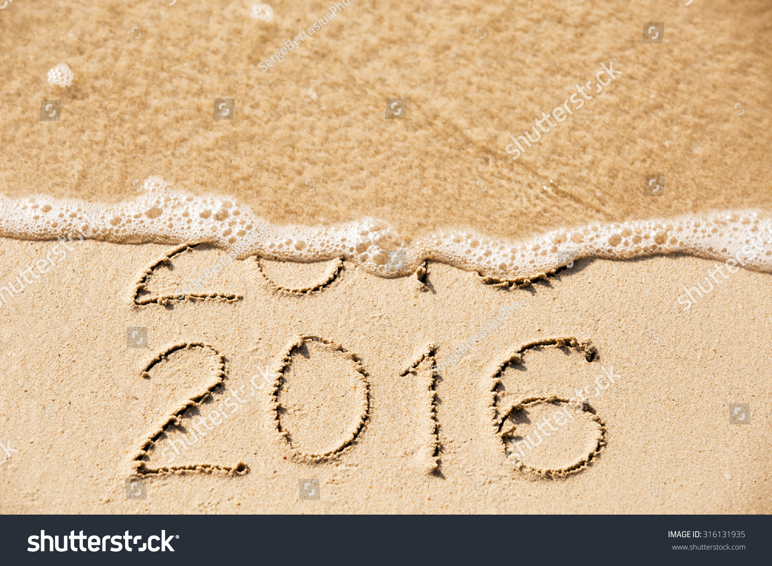 2015 2016 inscription written in the wet yellow beach sand being washed with sea water wave. Concept of celebrating the New Year at some exotic place #316131935
