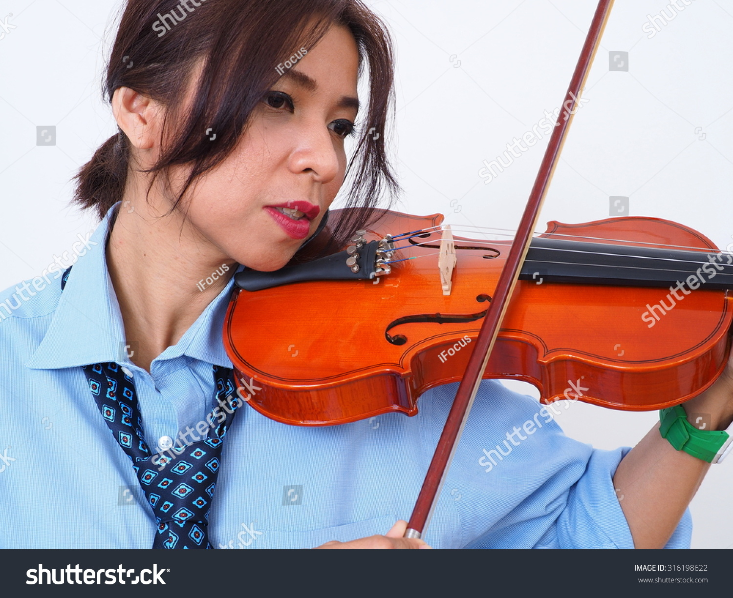 Modern Asian woman with undone tie plays violin