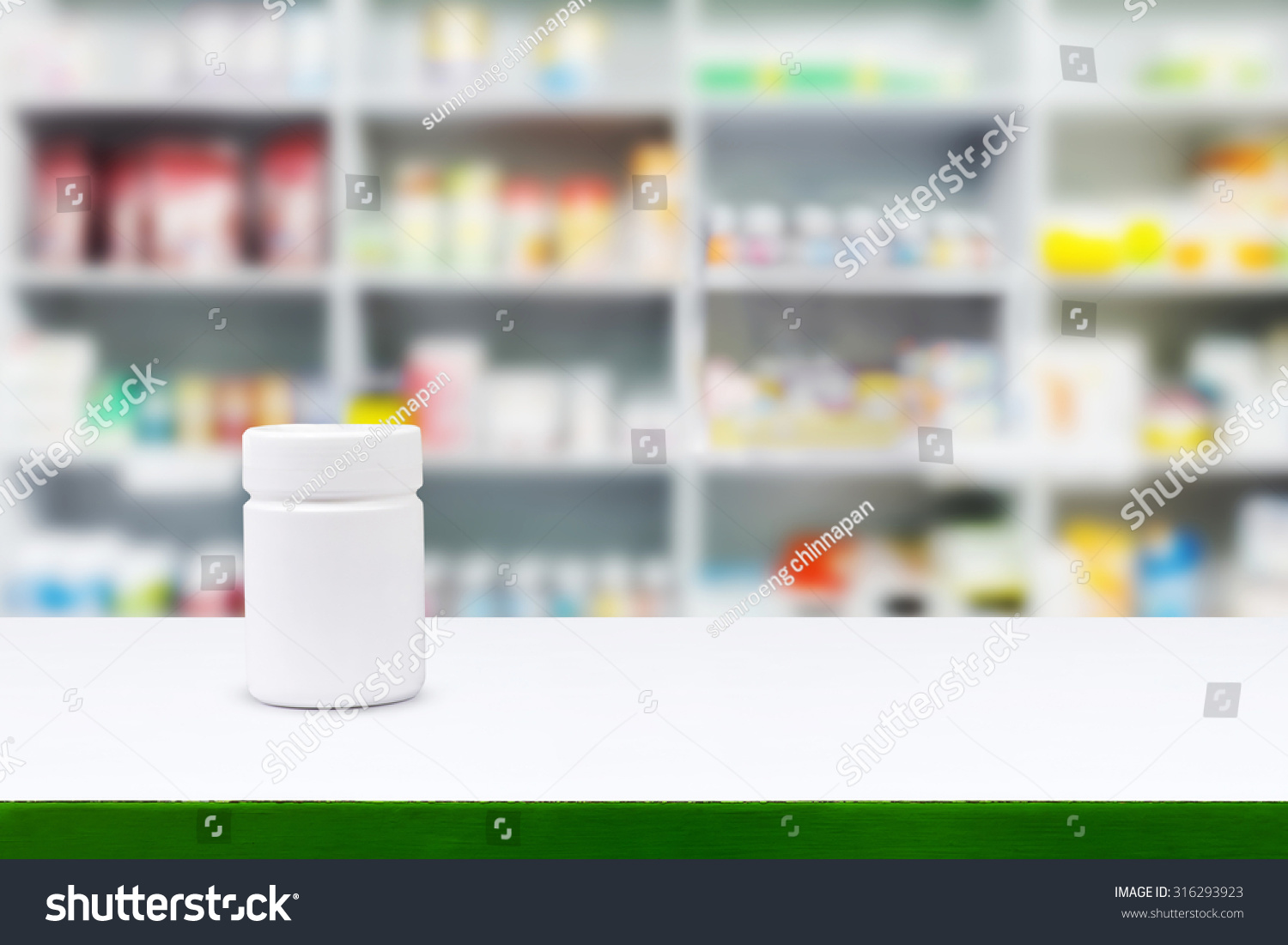 Blank white medicine bottle on counter with blur shelves of drug in the pharmacy drugstore background