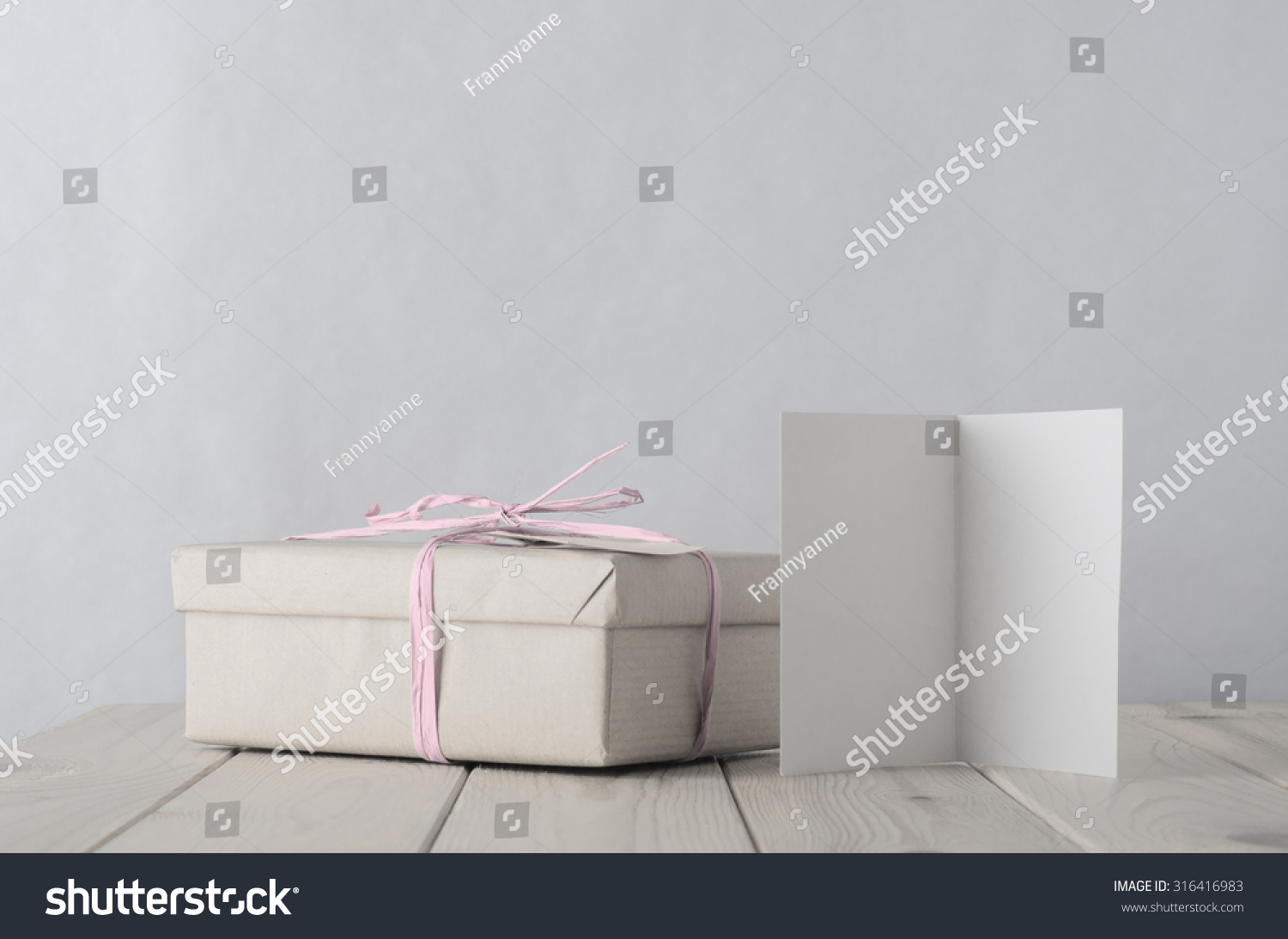 photo of a gift box simply wrapped in brown paper tied with pale icy pink raffia on an old. Black Bedroom Furniture Sets. Home Design Ideas