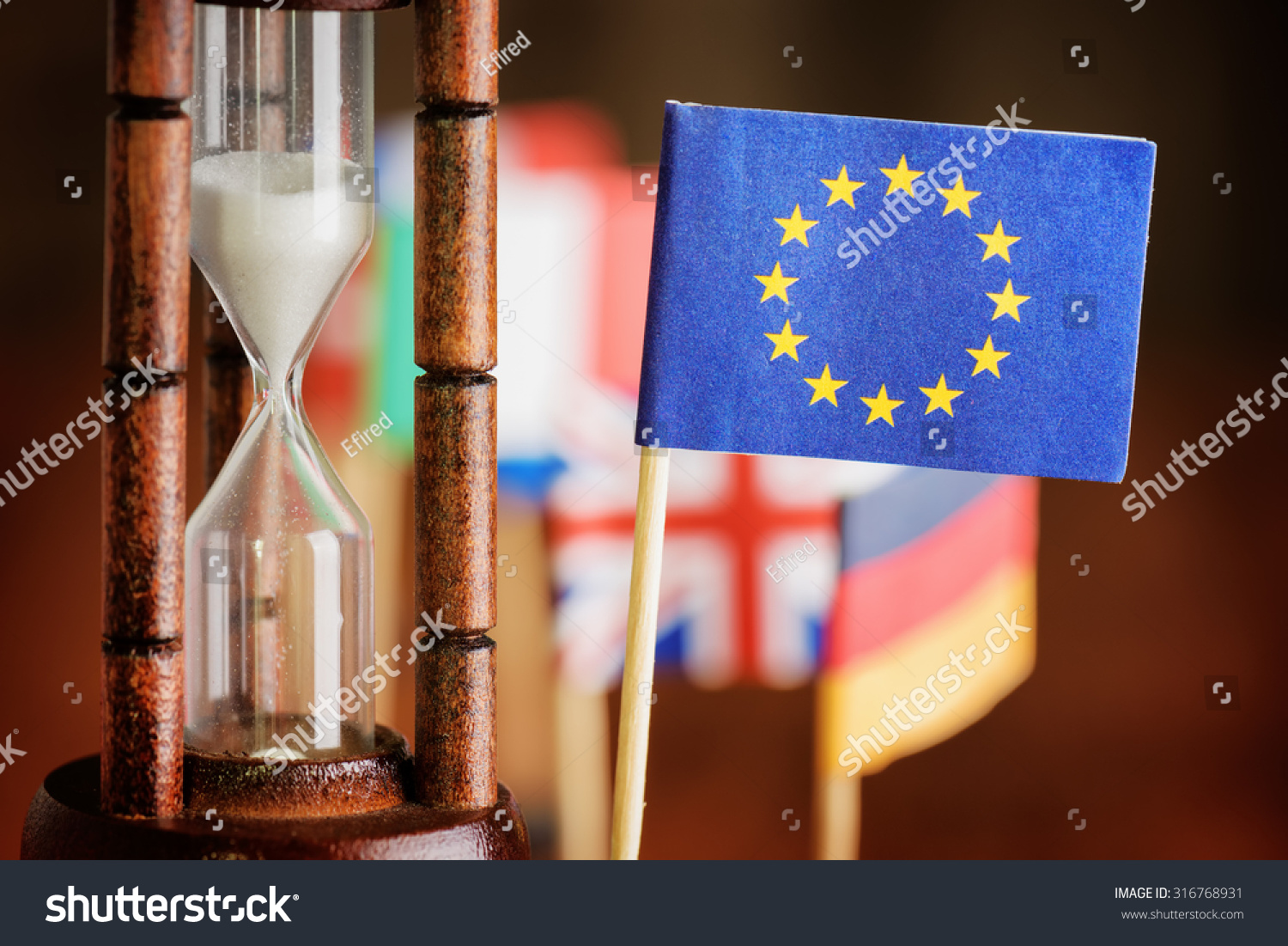Political concept with flag of the European Union (EU). Time is running out. Closeup view of hourglass and flag of the European Union (EU). Flags of European countries in background. #316768931