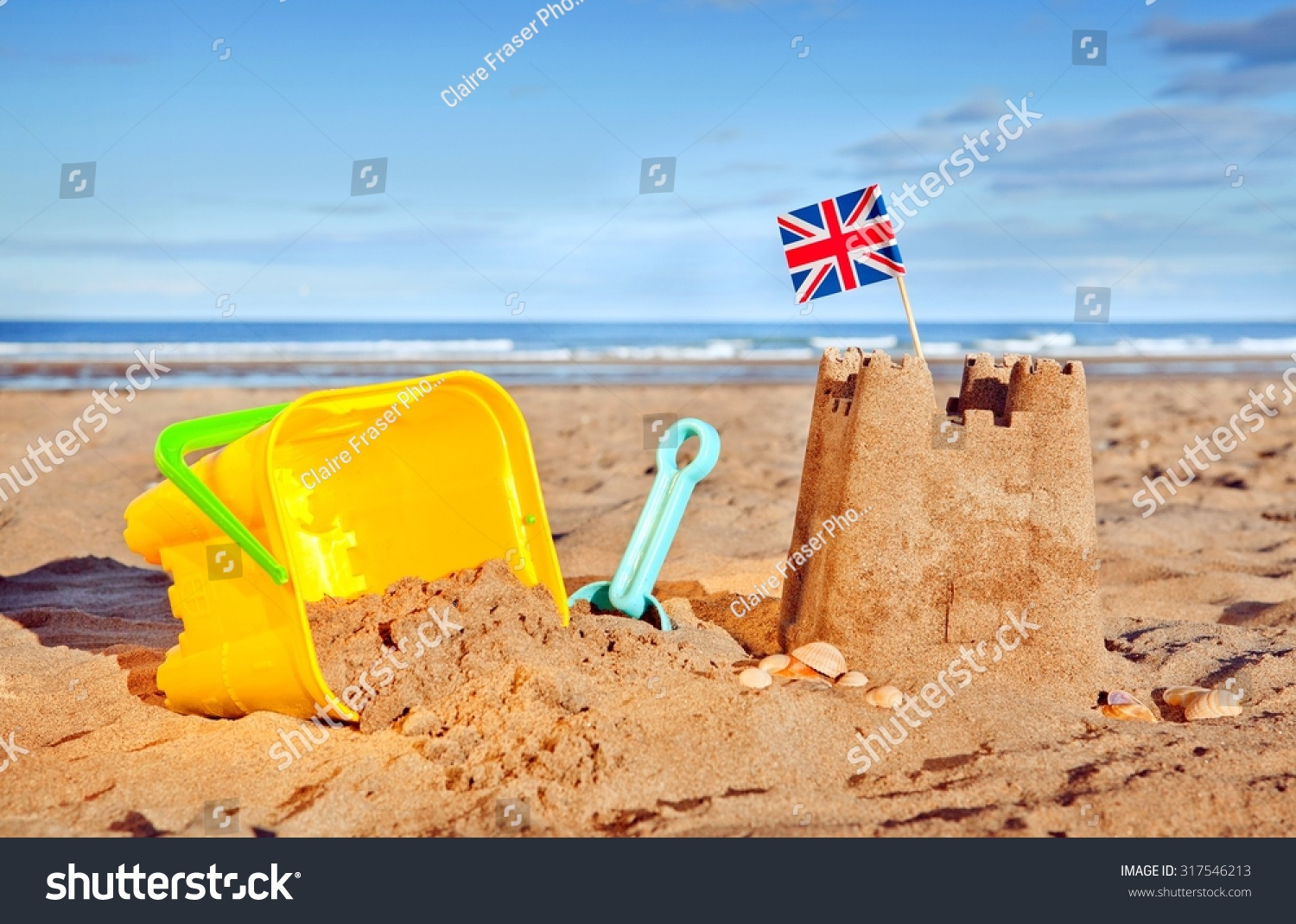 http://image.shutterstock.com/z/stock-photo-british-seaside-traditional-sand-castle-on-the-beach-with-bucket-and-spade-shells-and-union-jack-317546213.jpg