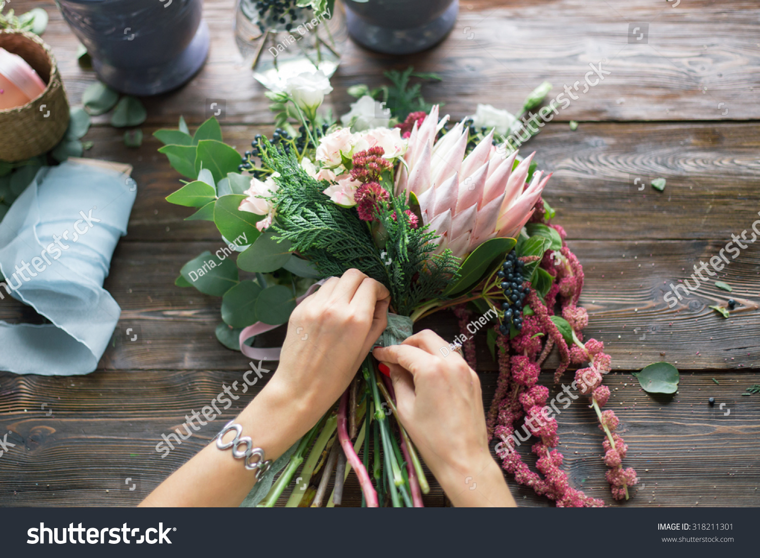 Florist at work: pretty young blond woman making fashion modern bouquet of different flowers #318211301