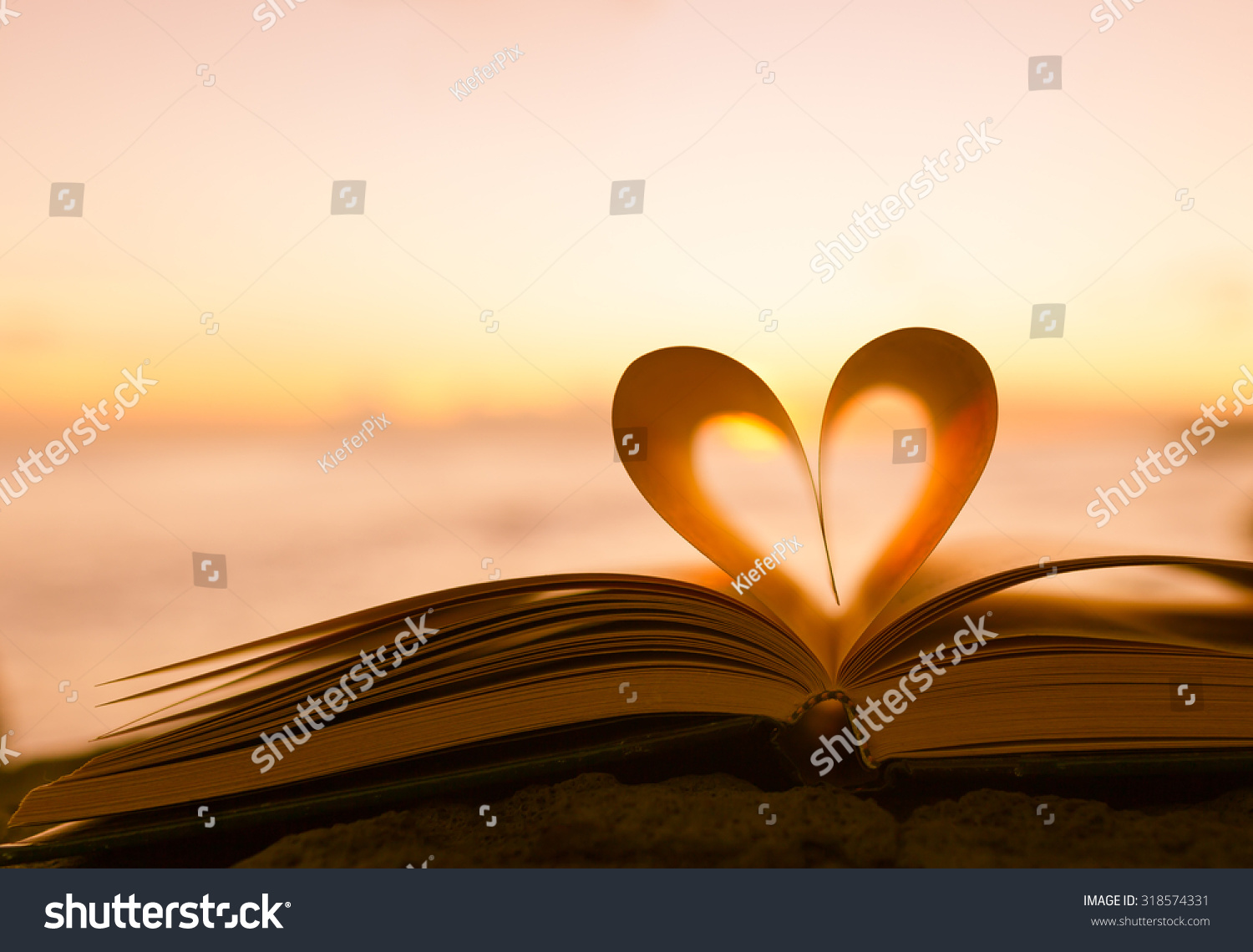 Heart from a book page against a beautiful sunset