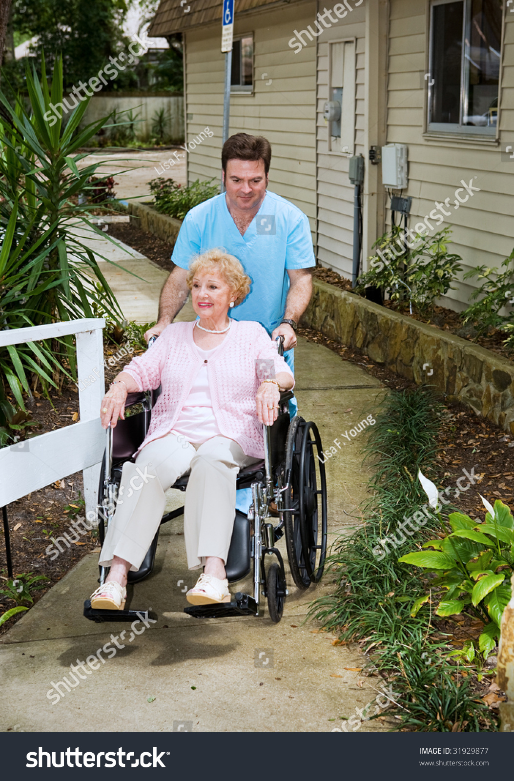 Senior Woman Arrives At A Nursing Home And Is Wheeled