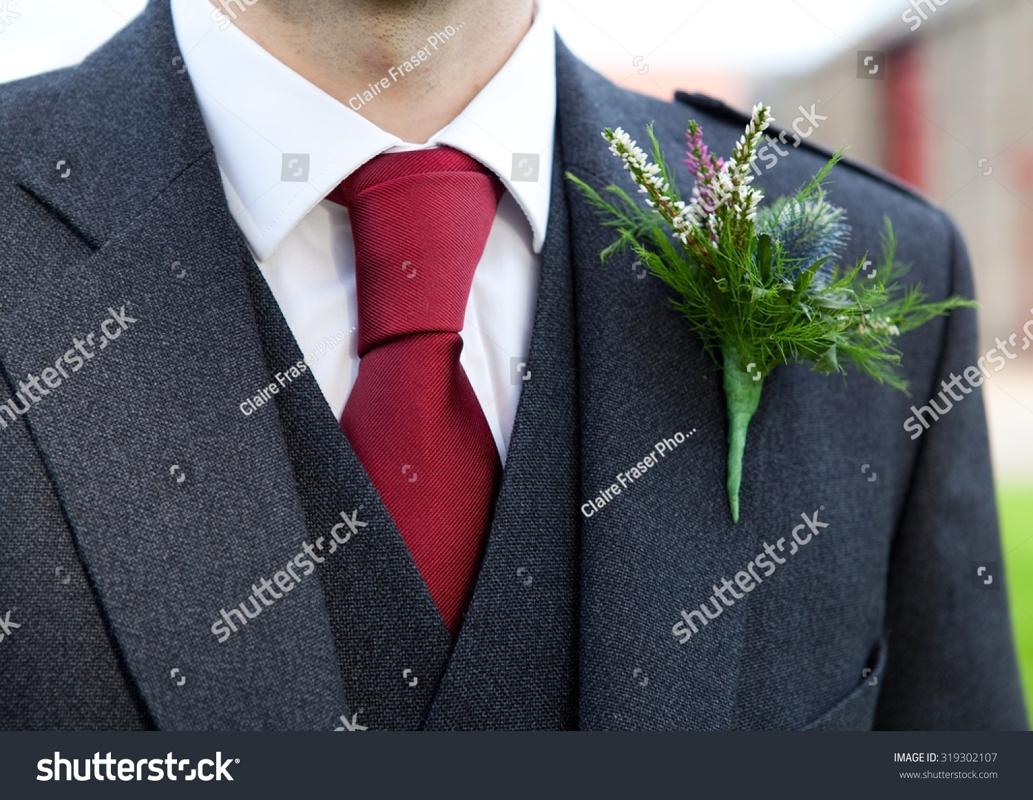 Groom in suit with blue thistle button hole flower close up