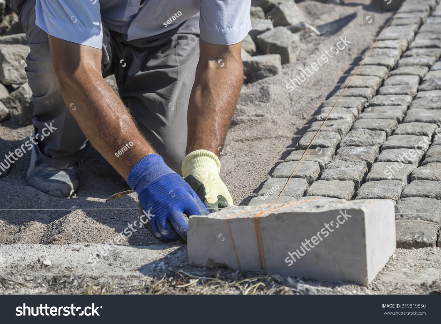 Laying Natural Stone : Worker installing granite cubes for pathway laying