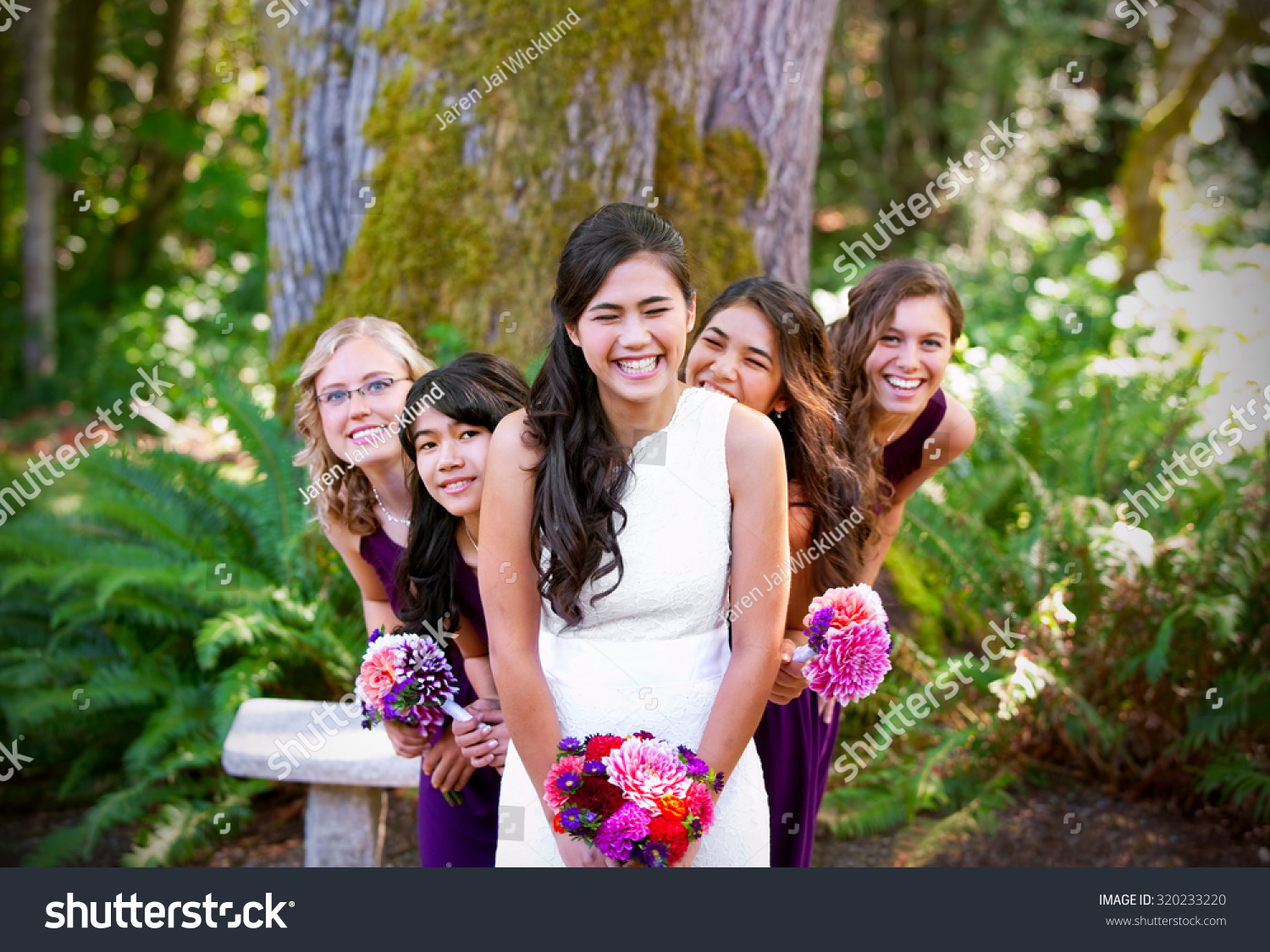Beautiful biracial young bride smiling her stock photo 320233220 beautiful biracial young bride smiling with her multiethnic group of bridesmaids in purple dresses ombrellifo Gallery