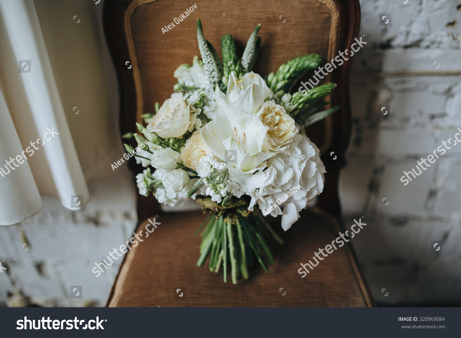 Bridal bouquet white flowers greenery on stock photo edit now bridal bouquet of white flowers and greenery is on a vintage chair against a white brick izmirmasajfo