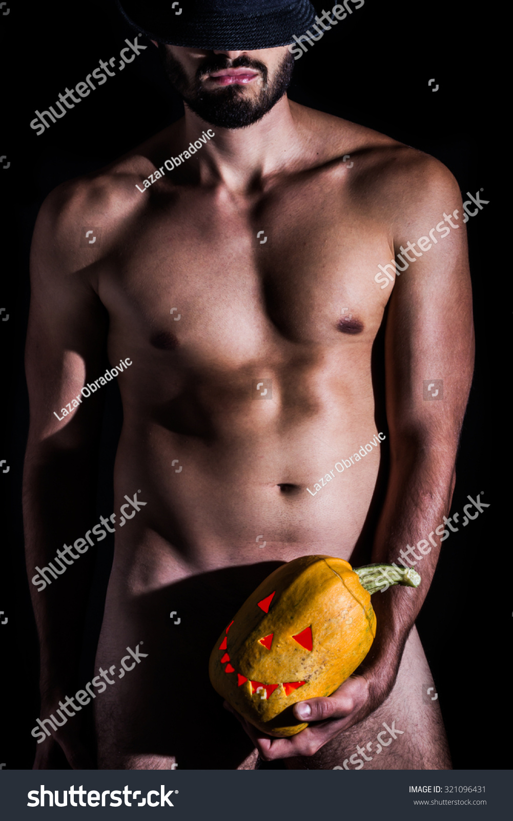 naked man hat holding creepy carved stock photo (royalty free