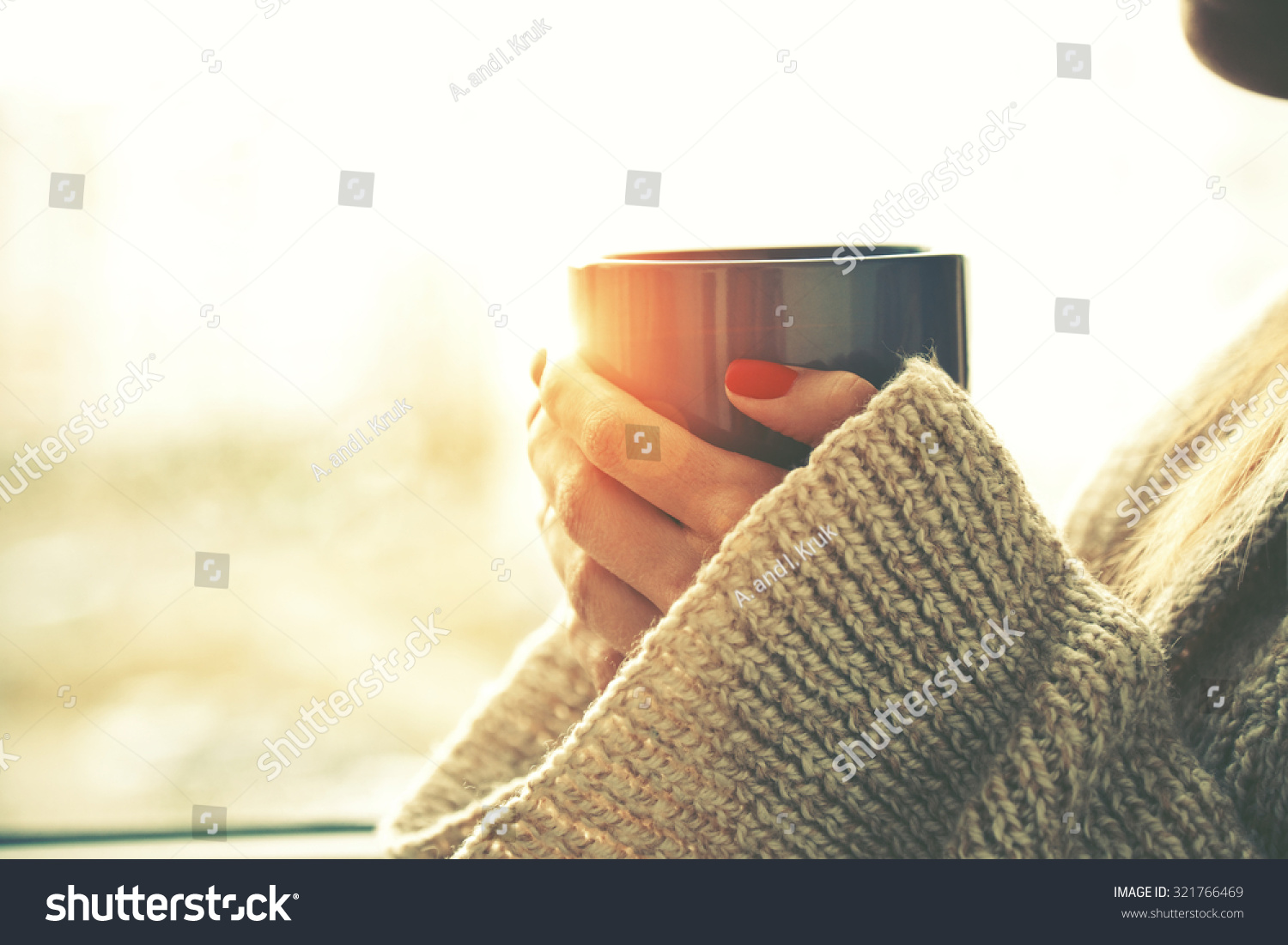 hands holding hot cup of coffee or tea in morning sunlight #321766469