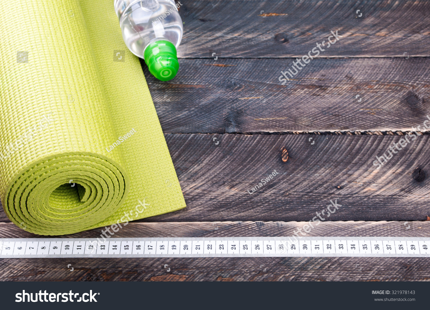 3475fdcbe32bb Yoga mat, water bottle and centimeter on a wooden background. Equipment for  yoga. Concept healthy lifestyle. Selective focus Stock Photo