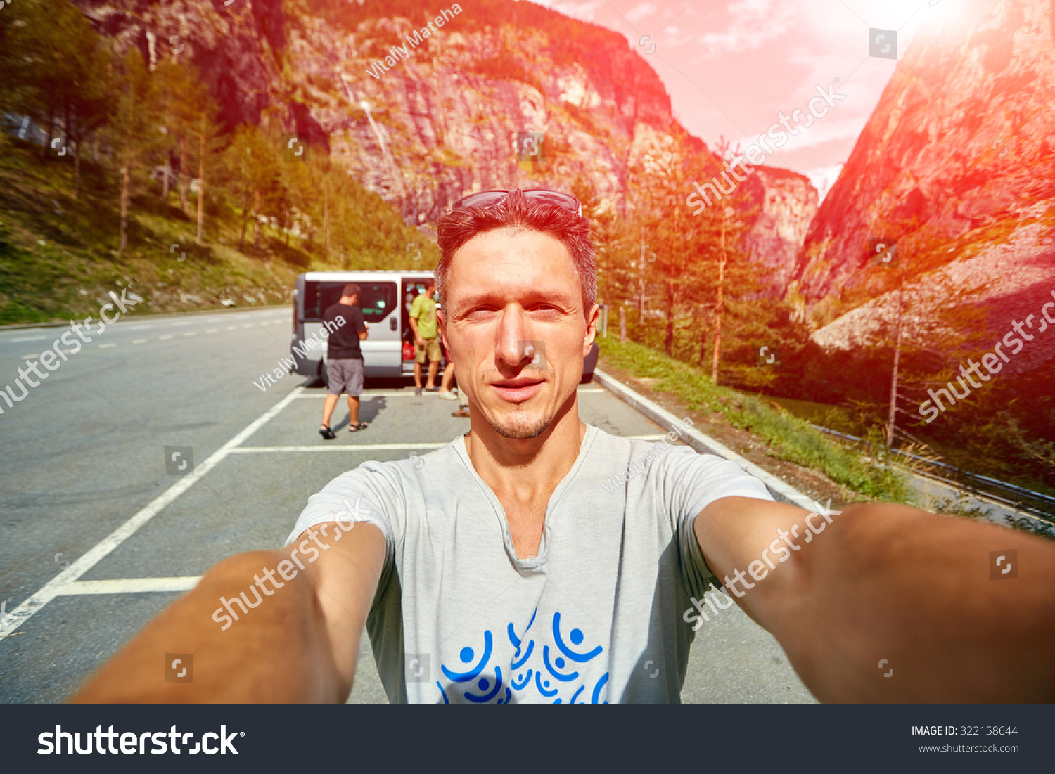 young  man make selfie on the morning mountains background. Man dressed in a white t-shirt and white sunglasses #322158644