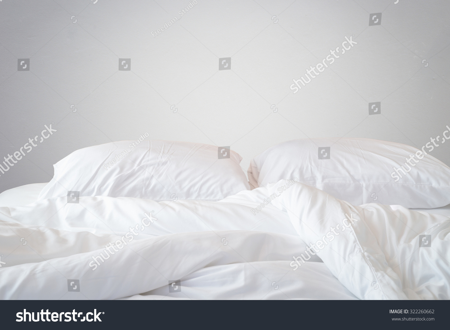 Close up white bedding sheets and pillow on natural stone for Wall pillow for bed