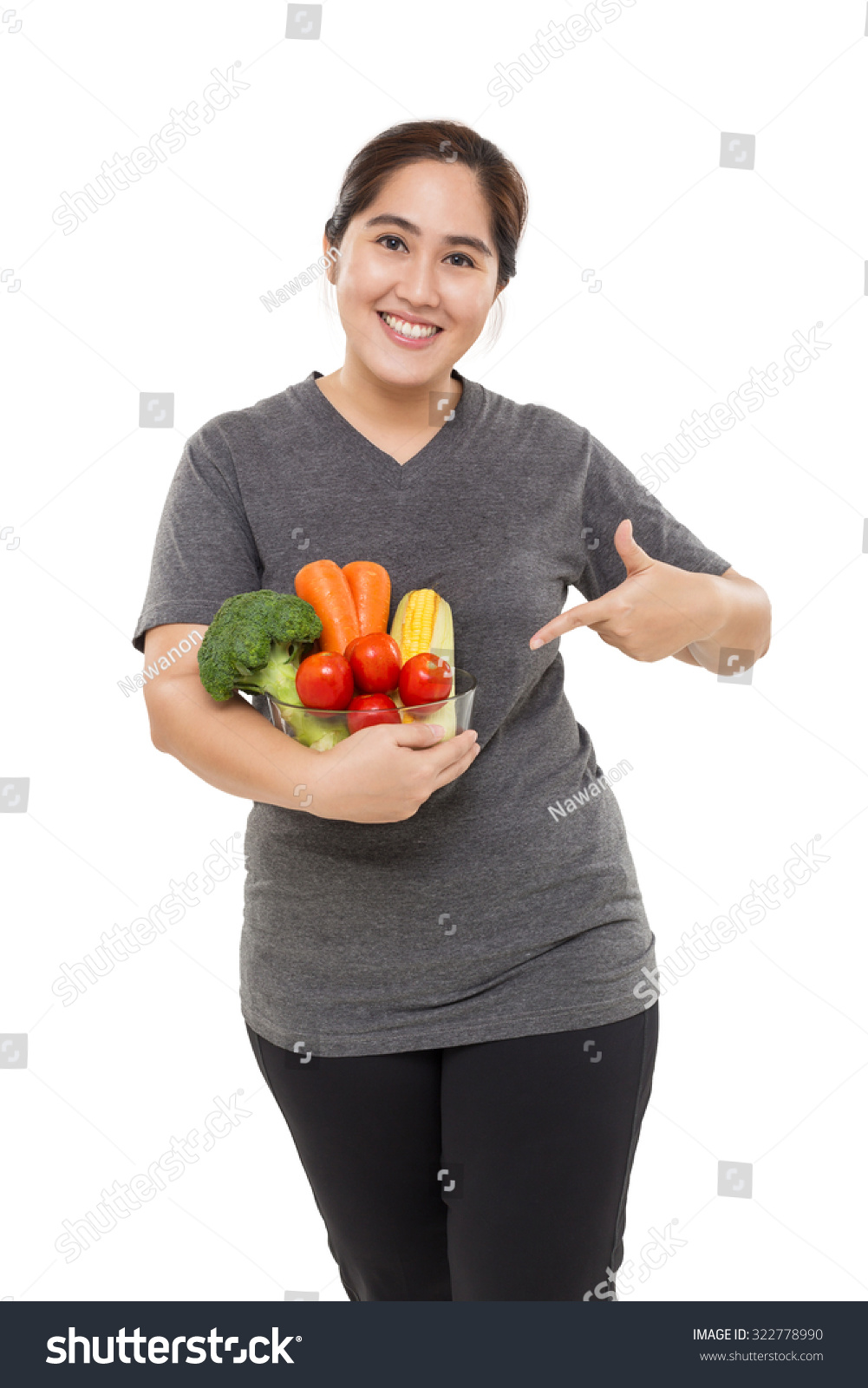 Fat Asian woman holding a bowl of vegetable isolated on white background.  Pointing finger at