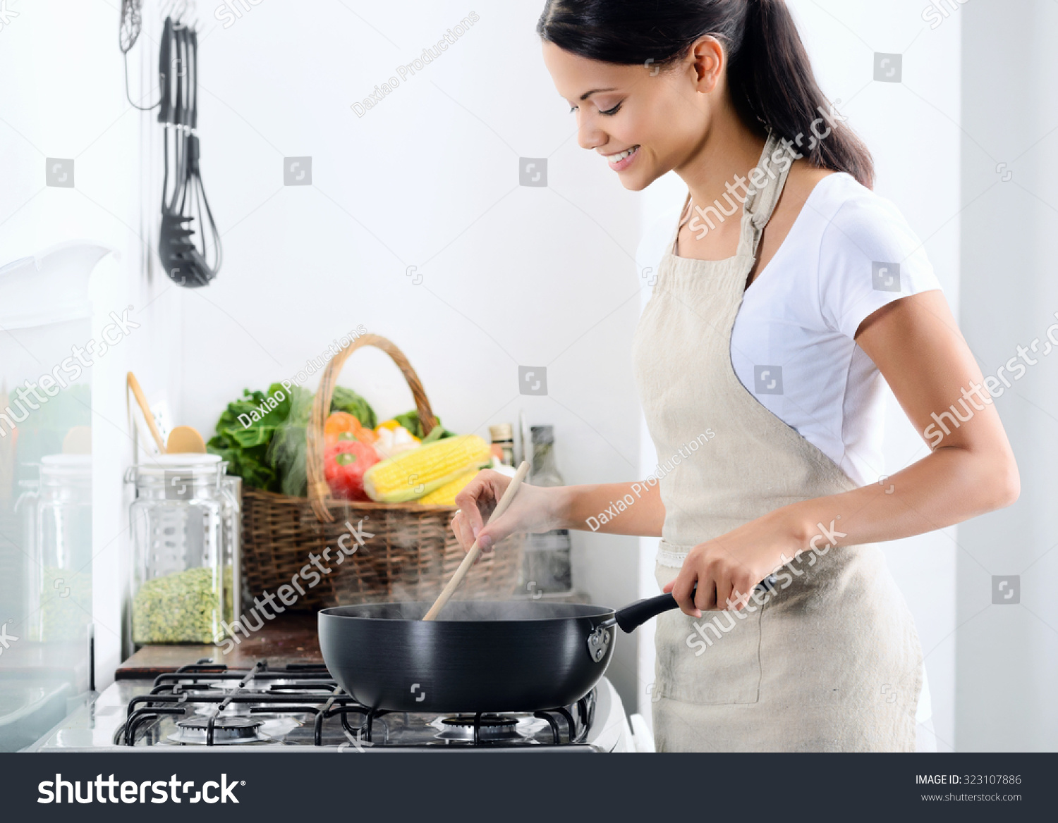 Cooker In Kitchen ~ Woman standing by stove kitchen cooking stock photo