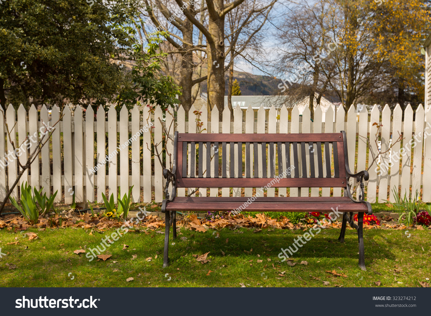 wooden bench in the garden in front of the white fence | EZ Canvas