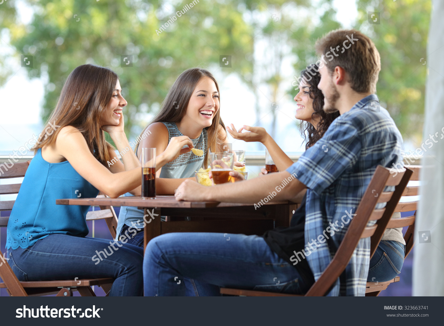 Group four friends talking drinking sitting stock photo for The terrace group