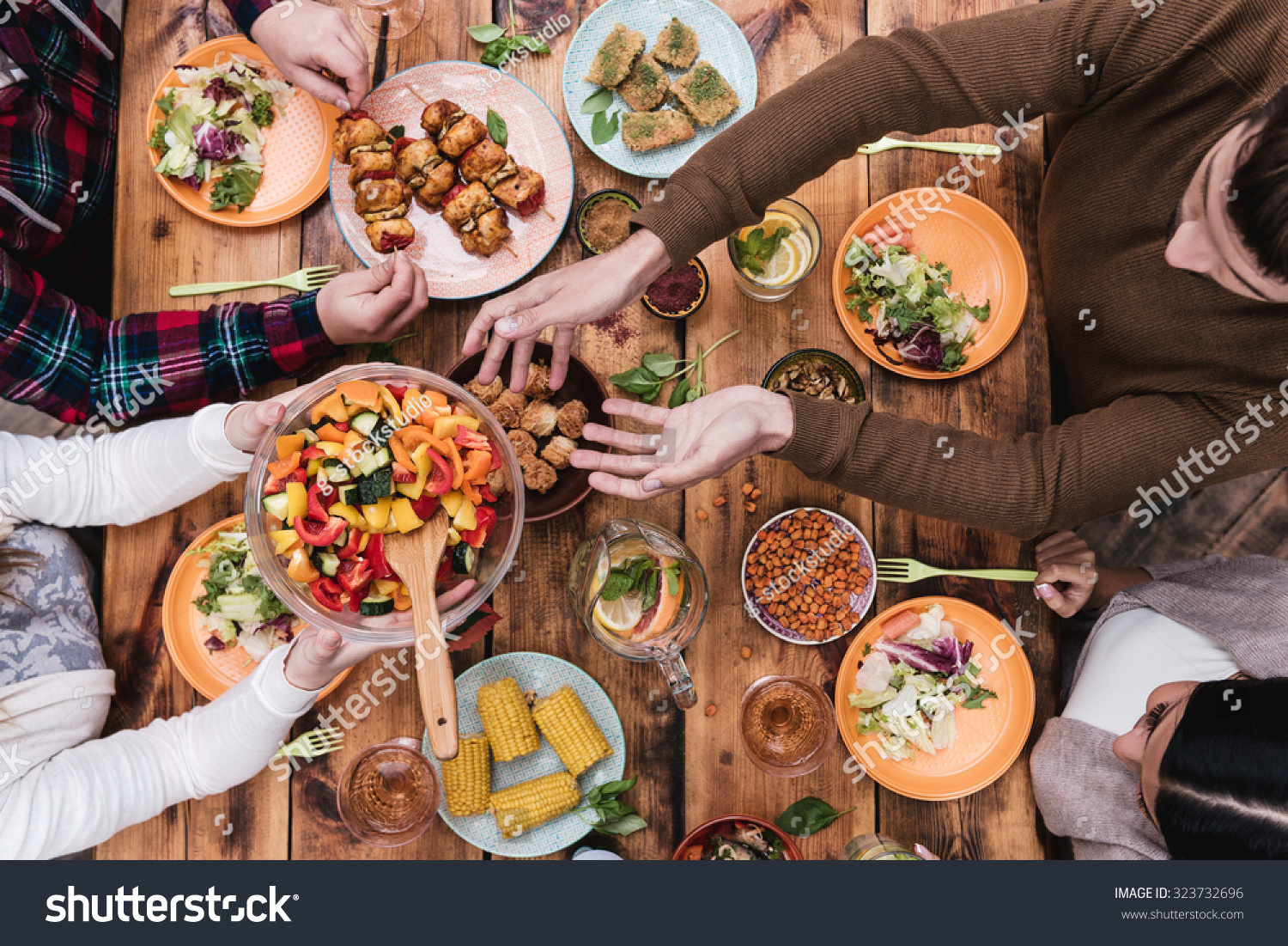 Friends Having Dinner Top View Four Stock Photo 323732696  : stock photo friends having dinner top view of four people having dinner together while sitting at the rustic 323732696 from www.shutterstock.com size 1500 x 1101 jpeg 970kB
