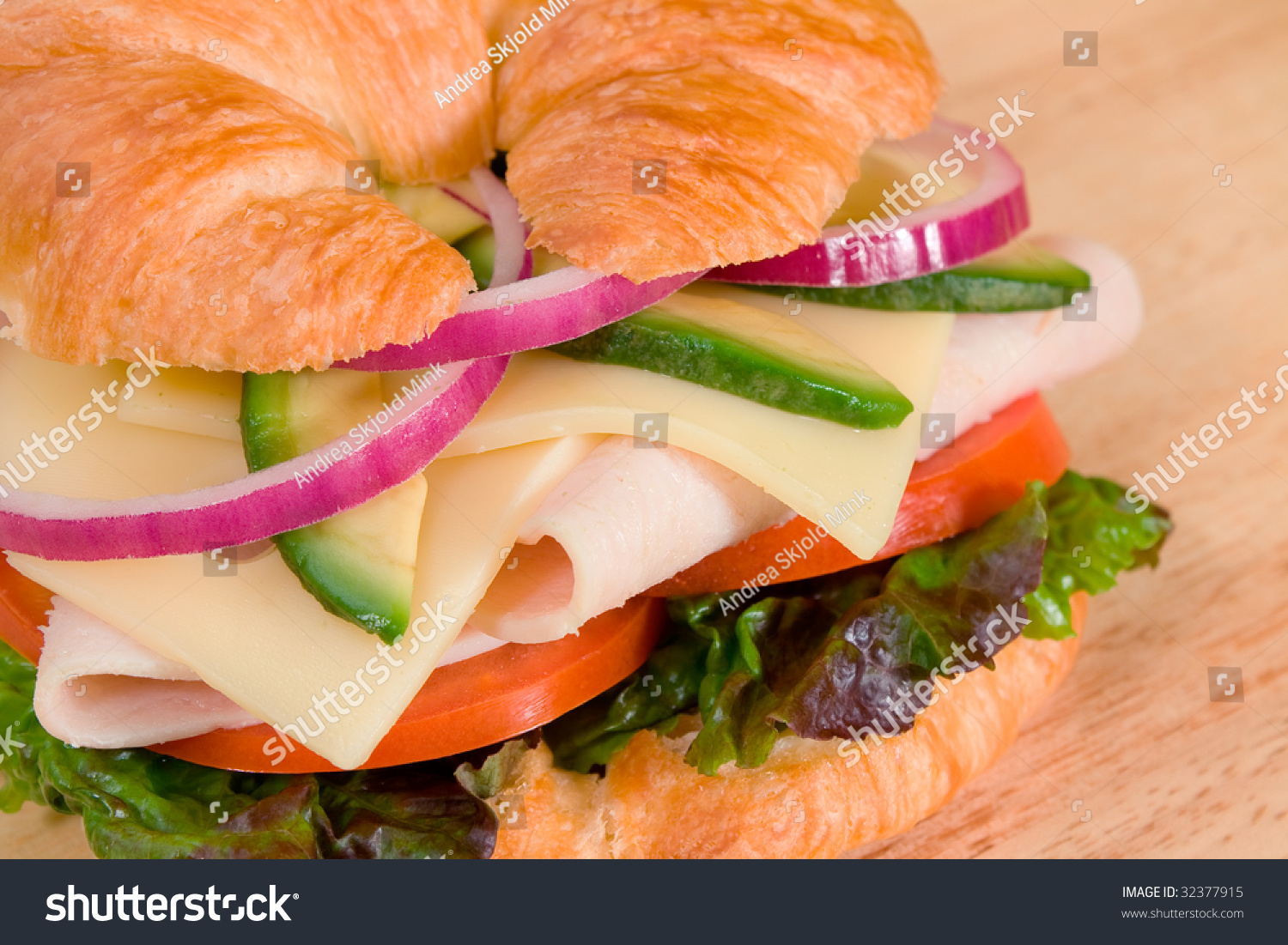 Turkey sandwich on a croissant with swiss cheese, avocado, tomatoes ...
