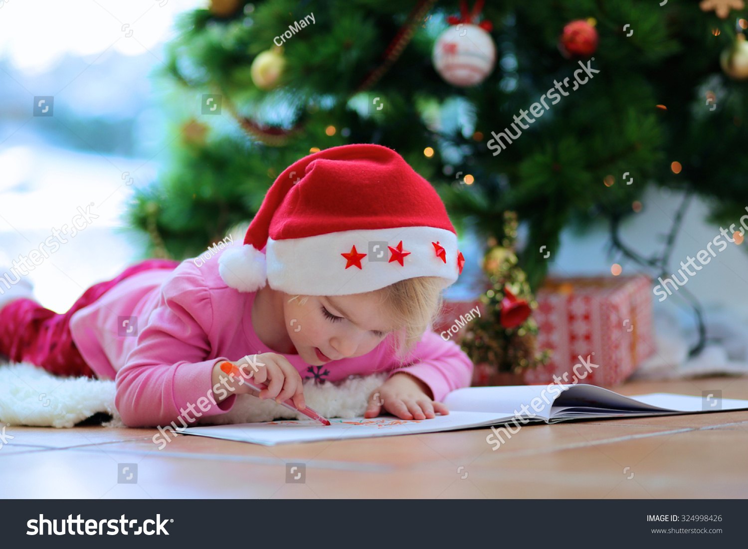 Cute little kid writes letter santa stock photo royalty free cute little kid writes letter to santa adorable toddler girl in santa hat lying on spiritdancerdesigns Images