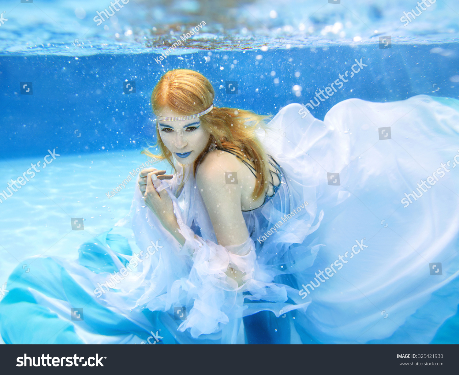 Blonde Young Beautiful Woman As Air Element Underwater In The Swimming Pool