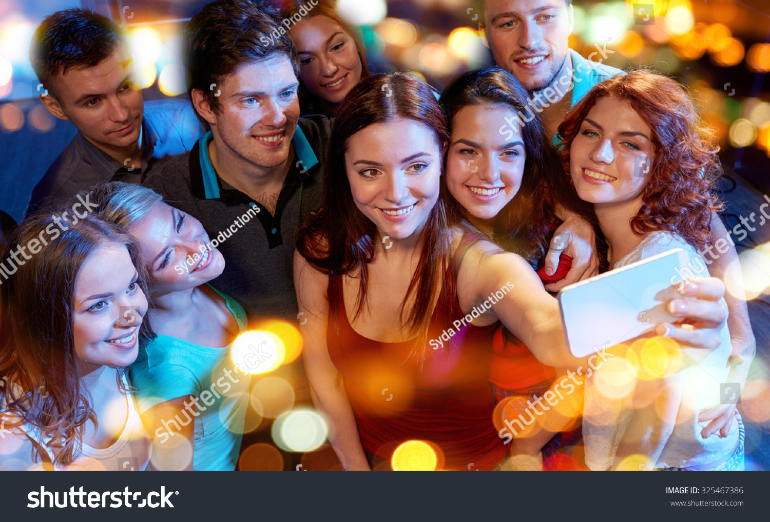 party technology nightlife and people concept smiling friends with smartphone taking selfie in club