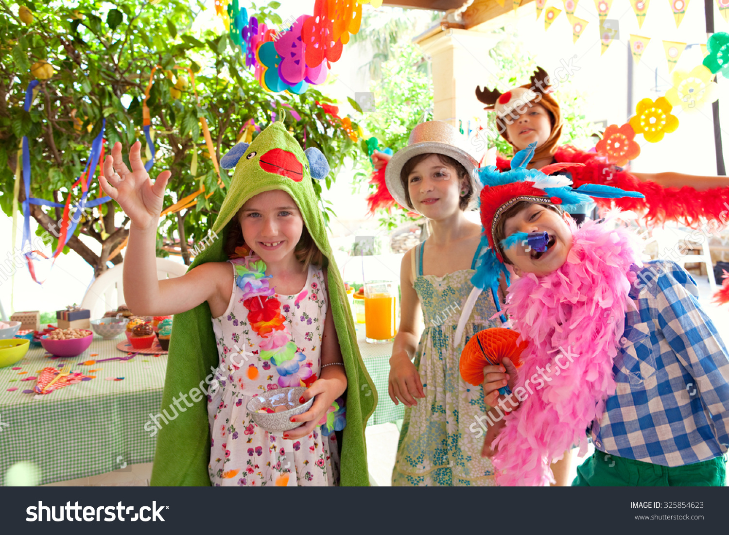 5ab0cc9f6 Group of children dressing up in improvised fancy dresses at a colorful  birthday party in a