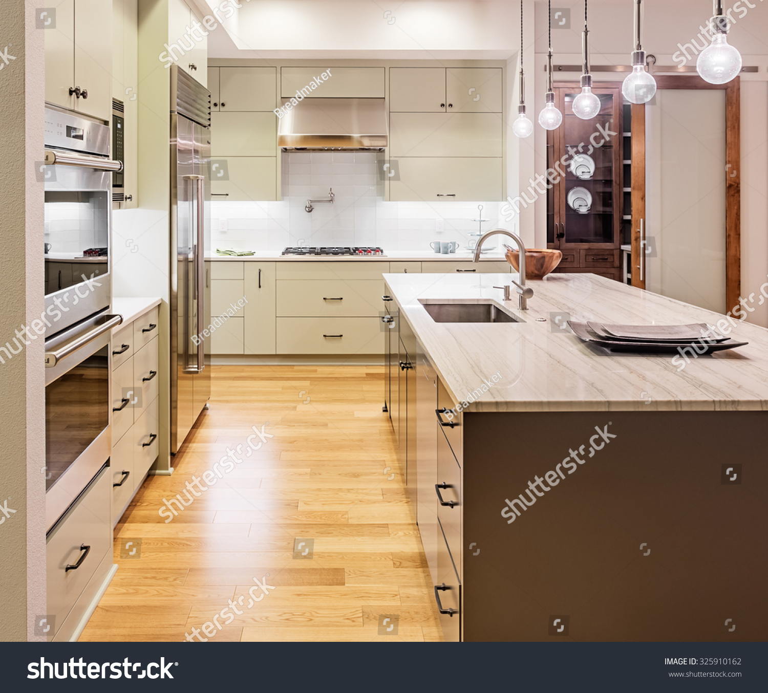 Kitchen Interior With Island, Sink, Cabinets, And Hardwood