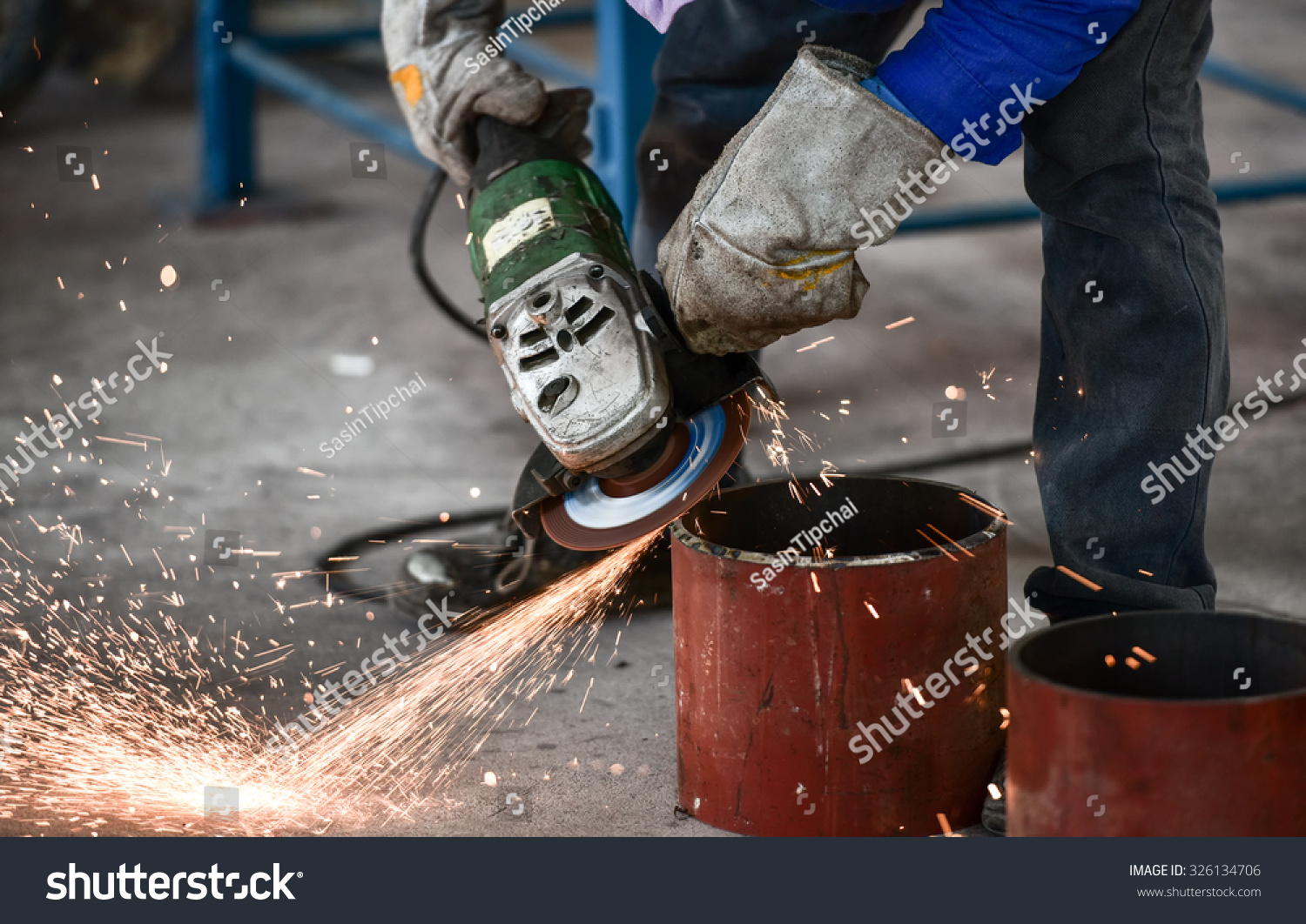 Electric wheel grinding on steel pipe in factory stock