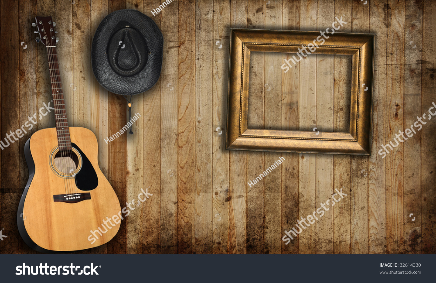 cowboy hat guitar and empty picture frame against an old barn background