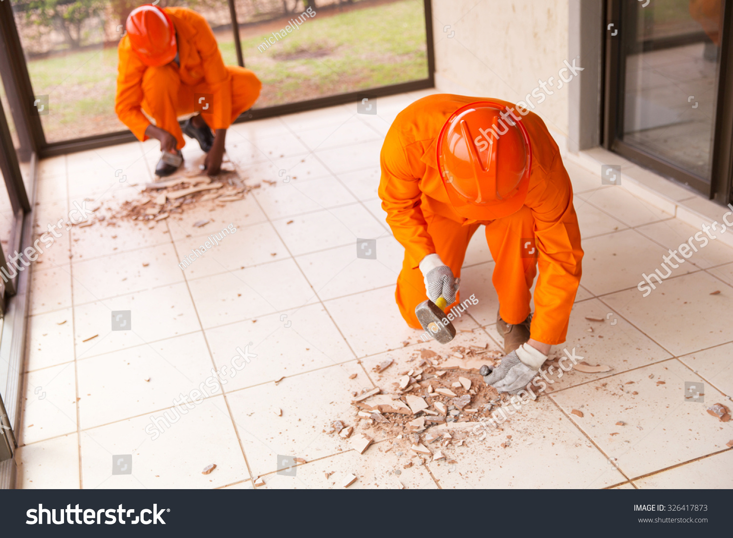 Contractors removing old floor tiles using stock photo 326417873 contractors removing old floor tiles using hammer and chisel dailygadgetfo Image collections