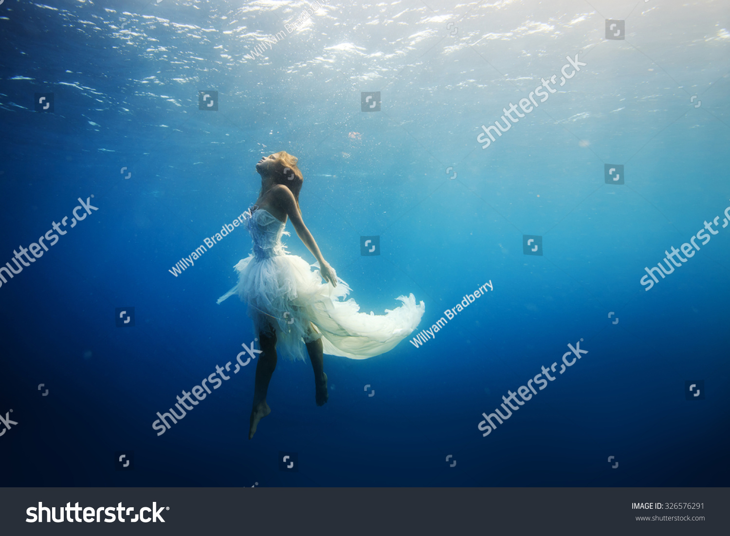 A girl wearing fashion white dress underwater in blue deep A Wild Ocean Scenery without fish