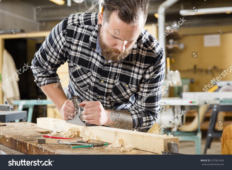 Hard working craftsman working planer workshop stock photo for Working man tattoo