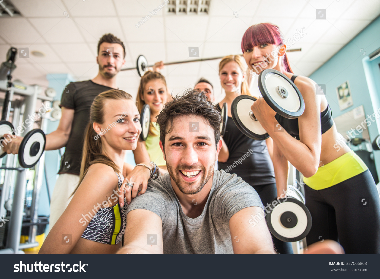 Group of sportive people in a gym taking selfie happy