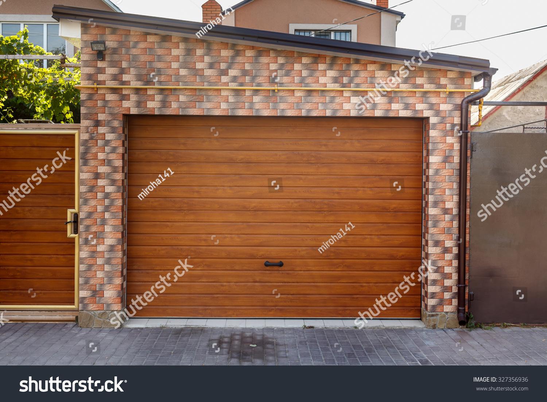 1100 #ACAA1F Dark Wooden Garage Door With Colored Brick Wall Background Stock Photo  wallpaper Dark Wood Garage Doors 36951500