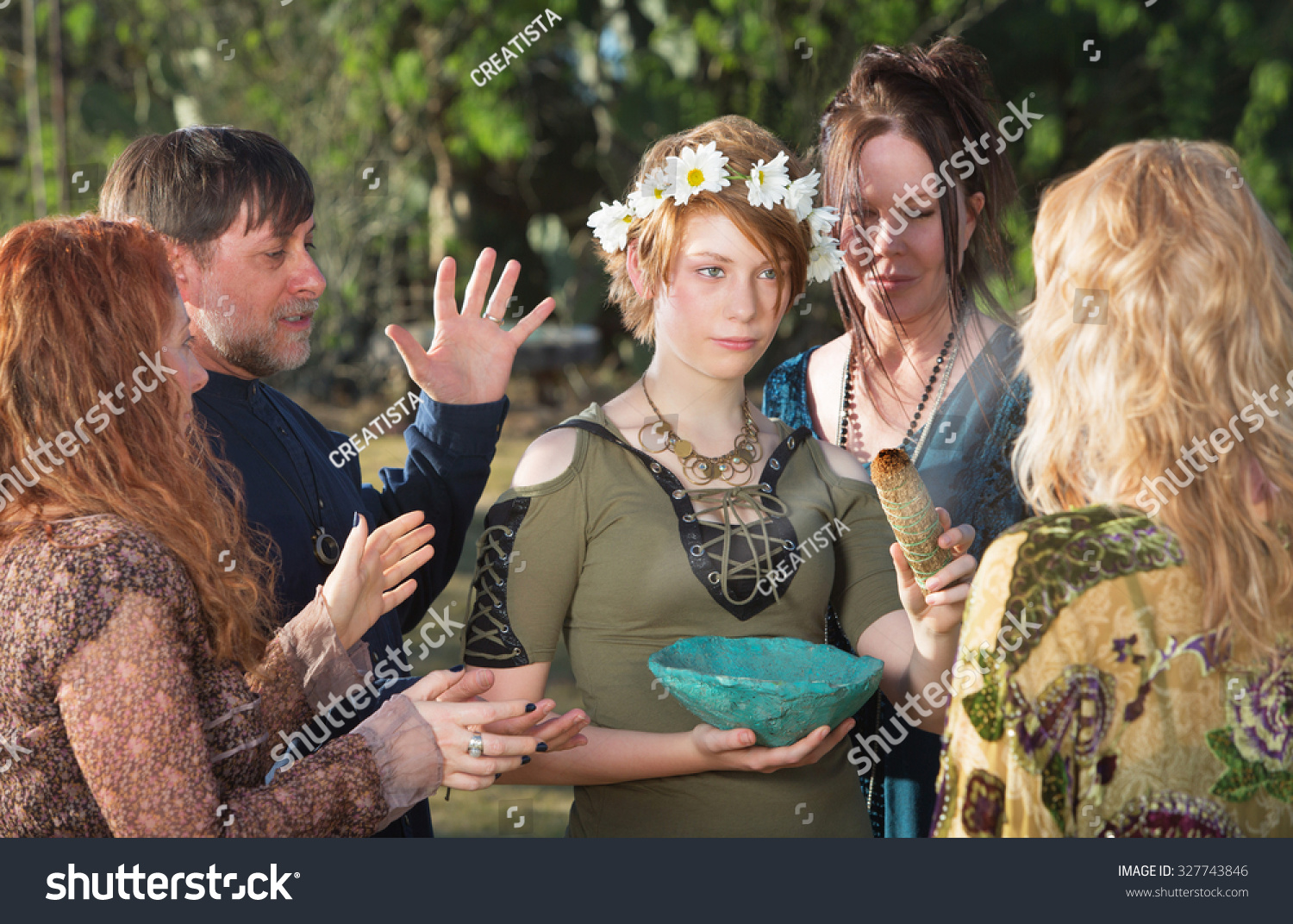 Group of witches outdoors doing an initiation ritual